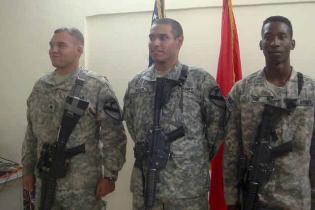 BAGHDAD - Spc. Coy Powell, left, a Signal Support Systems Specialist; Spc. Mario Fabian, center, a Medic; and Pfc. Louis Love, right, a Cav. Scout; await to receive coins from the Dep. Cdr. of ITAM Police, on May 25, 2011 at JSS Shield in Baghdad, Iraq.