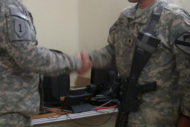 BAGHDAD - Spc. Coy Powell, a Signal Support Systems Specialist, of C Trp, 6-9 Cav., 2nd AAB, 1st Inf. Div., USD-C, is congratulated by Col. Krall, the Dep. Cdr. of the ITAM-Police, as he receives a coin on May 25, 2011