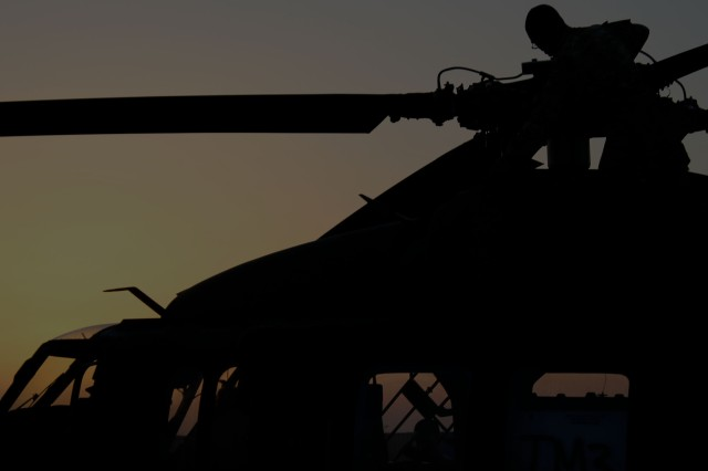 CAMP MARMAL, Afghanistan - Sgt. Michael Copeland, a crew chief assigned to Company A, TF Lobos, 1st Air Cav. Bde., 1st Cav. Div., inspects the rotor blades of UH-60L Black Hawk helicopter prior to a maintenance test flight as the sun sets, here, June 2.