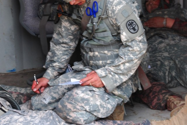 Spc. Steven Kou documents the status and vitals of each casualty.