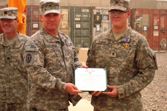 BAGHDAD - Brig. Gen. Paul LaCamera, DCG-Ops., 25th Inf. Div., poses for a picture with Spc. Christian Cowan, a Combat Medic with Apache Troop, 6-9th Cav., 2nd AAB, 1st Inf. Div., USD-C, after he award him with the Purple Heart on 2 Jun.