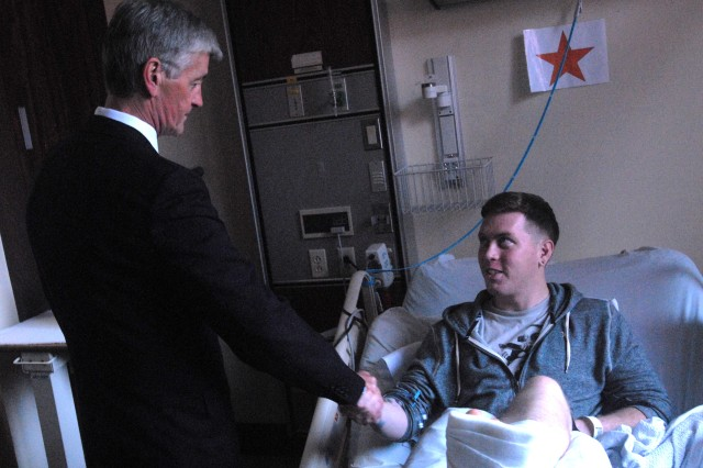 Secretary of the Army John McHugh thanks Private 1st Class Kyle Foster, a Soldier wounded while deployed with the 25th Infantry Division's 3rd Brigade, who is recovering at Tripler Army Medical Center, for his service to his country. McHugh took the time to meet with several wounded warriors during a recent visit to the Pacific which kicked off in Hawaii.