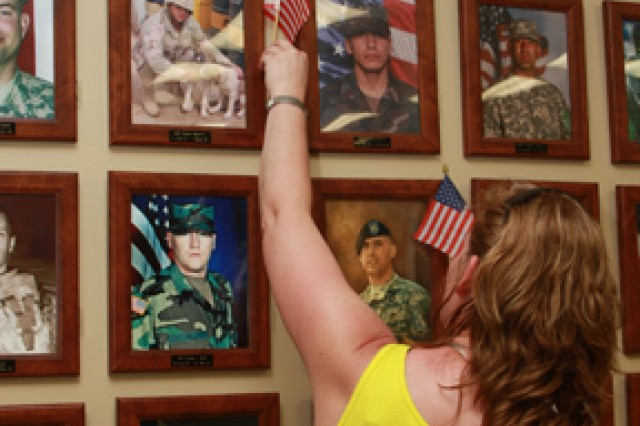 Beate Medina places a flag on her husband's photo in the Fort Hood SOS Center Hall of Remembrance May 30, 2011, to mark Memorial Day.