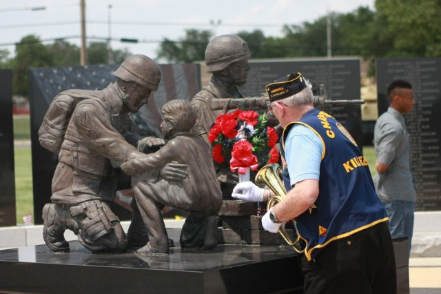 Retired Sgt. Maj. Theron Johnson lays flowers before playing TAPS May 30, 2011, at the 1st Cavalry Division Memorial.