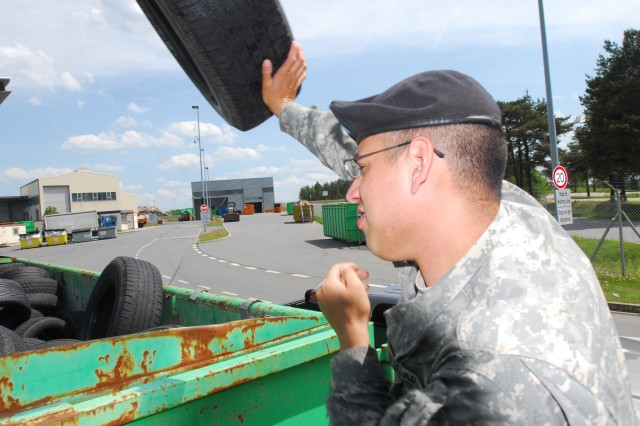 Spc. Ricardo Hurtado, 574th Quartermaster Support Company, heaves an old tire into the storage container at the Central Recycling Facility at the Grafenwoehr Training Area, Germany.