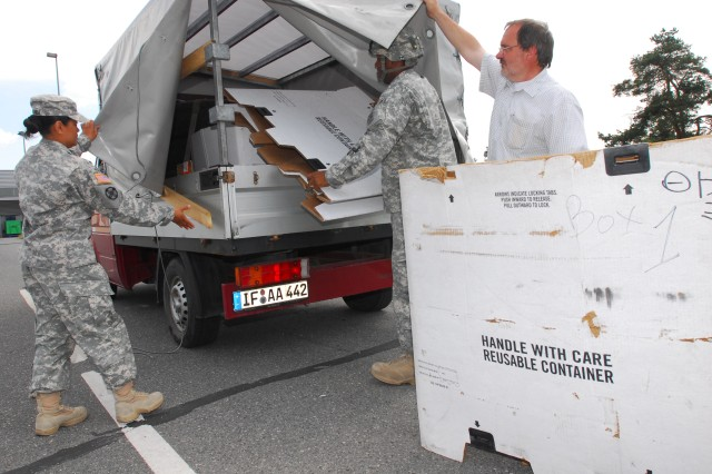 Sgt. Ralph Johnson and Sgt. Miranda Aladia, 172nd Headquarters, Headquarters Company, deliver recyclable materials to the Central Recycling Facility at the Grafenwoehr Training Area, Germany. Claus Dieter Englhardt, an engineering technician at the plant, provides direction on proper disposal of the materials.