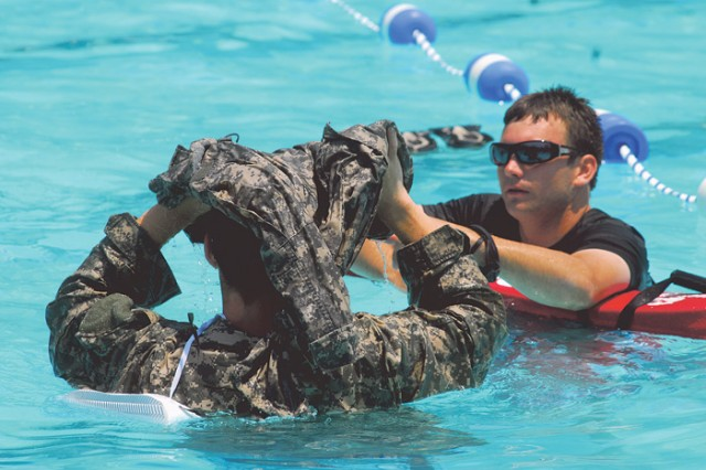 A lifeguard monitors as a cadet converts his pants into a flotation device by trapping a pocket of air.