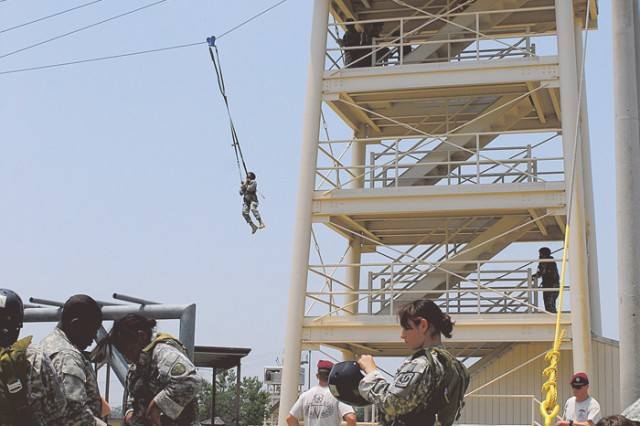 Cadets strap on gear and prepare for tower jumps. They are attached by a harness to a cable running from the tower to a berm roughly 200 meters away. Cadre from the Airborne School assisted the training.