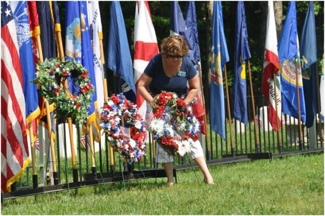 Kim Jordan of the Corpus Christi Council ladies auxiliary places a wreath in front of the cemetery during the Memorial Day Tribute at APG South (Edgewood) May 30.