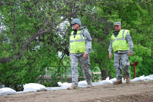Staff Sgt. Elsie Simonton and Sgt. Sean Windsor, of the North Dakota National Guard's 164th Engineer Battalion, patrol the dikes in Roosevelt Park in Minot, N.D., June 7, 2011. The dikes are patrolled 24 hours a day by two to three-Soldier teams.