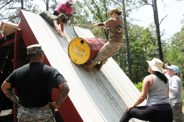 Sgt.1st Class Phil Scibelli watches on as a group of aviation spouses complete a team-building obstacle at the Leaders Reaction Course in an unconventional way at Fort Rucker's first Aviation Spouse Day.
