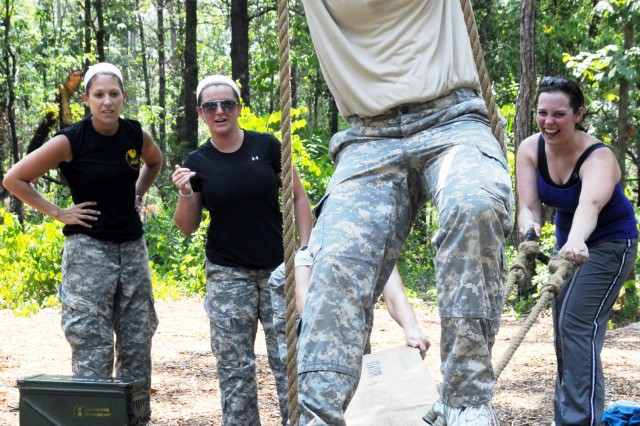 """Sabrina Johnson, military spouse, carefully gets across a """"mine field"""" obstacle at the Leaders Reaction Course while her teammates cheer her on."""