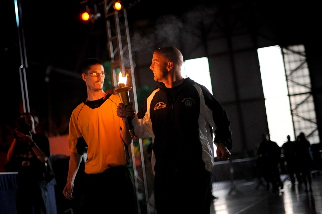Michael Cook, a Special Olympics of Washington track and field athlete, left, and Sgt. Randy Maynard of the Kennewick Police Department, carry the torch during the opening ceremony.