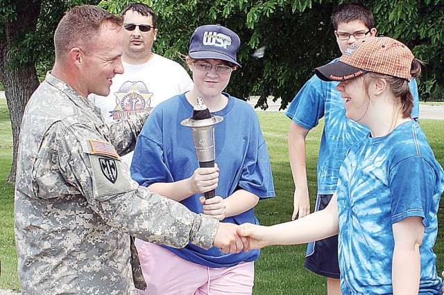 Lt. Col. Michael Mathews, commander, 97th MP Bn., left, shakes hands with Nicole Matthews, right, after passing the torch to Patricia Kalivoda, center, during the June 2 Special Olympics Law Enforcement Torch Run. Kalivoda and Matthews are members of the Junction City Pacesetters Special Olympics team.