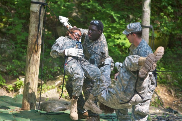 An Army Junior ROTC Cadet helps another unhook herself from a one-rope bridge during a stream-crossing exercise this week at Fort Knox, Ky., during Jackson Public Schools students' participation in the Junior Cadet Leadership Challenge program.