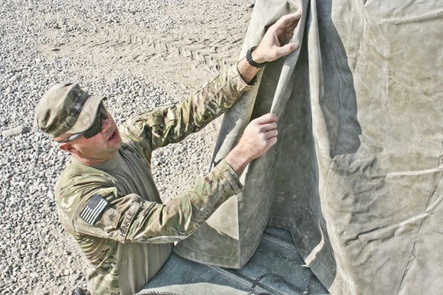 Sgt. Jared Henkle, a truck driver from Cincinnati, Iowa, with Company E, 1st Battalion, 133rd Infantry Regiment, Task Force Ironman, a part of the Iowa National Guard's 2nd Brigade Combat Team, 34th Infantry Division, Task Force Red Bulls, secures a tarp to a flatbed trailer Dec. 18, 2010, at Forward Operating Base Fenty in Jalalabad, Afghanistan. Henkle and another truck driver with Company E, Spc. Tyler Parker-Bellinger of Cedar Rapids, Iowa, recently found themselves on a resupply mission of 133rd Inf. Regt. Soldiers while under heavy fire.