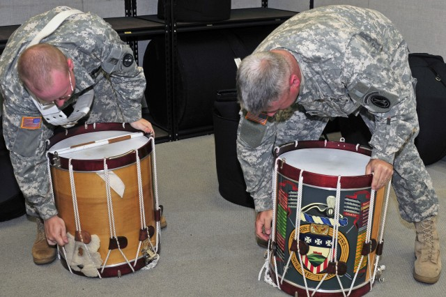 Sgt. 1st Class Richard Ruddle (right) and his son Staff Sgt. Andrew Ruddle (left), snare drum players for the Fife and Drum Corps, 3d U.S. Infantry Regiment (The Old Guard), tighten their drums to perfect the drums' pitches. FDC entertains millions of people in major parades, pageants and historical celebrations throughout the United States, and has served America as a goodwill ambassador as far away as Europe, Australia and Canada.