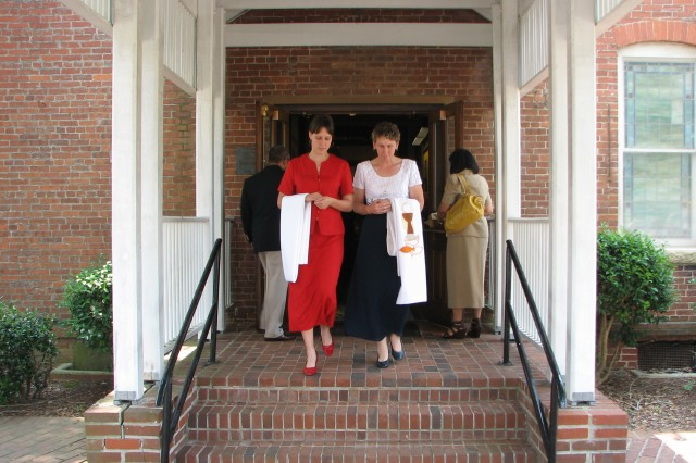 Britney Ferber (left), 16, and her mother, Jan Ingram, Garrison Chapel Office religious education contractor, carry out the altar linen linens and colors as part of the Fort McPherson Post Chapel decommissioning ceremony Sunday. The removal of the sacred items was the final step in closing down the chapel.