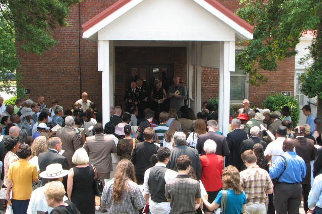 Parishioners of the Fort McPherson Post Chapel gather outside its doors for one last song following the chapel's decommissioning ceremony Sunday. The chapel had served as a place of worship for 122 years, nearly all of the post's 126 year history.