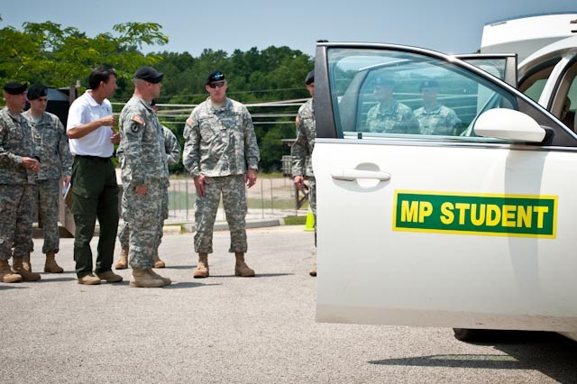 Gen. Robert Cone, U.S. Army Training and Doctrine Command commanding general, speaks with Soldiers and instructors about a patrol car used for Military Police training at the U.S. Army Military Police School's Stem Village. Cone visited Fort Leonard Wood, Mo., June 9, to meet with Maneuver Support Center of Excellence senior leaders, speak with Soldiers and to observe training that demonstrates the post's outstanding contributions to the Army's and TRADOC's focus areas.