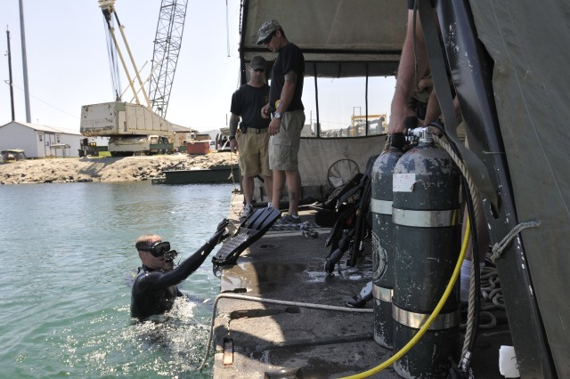 Mater Diver Sgt. 1st Class Kurt Langley (left) of the 86th Engineer Dive Detachment, Special Troops Battalion, 7th Sustainment Brigade, evaluates diving supervisor, Sgt. David Craig, during a deep water dive training exercise while Sgt. Daniel Ormond (diver in water at far left) listens. Craig and Ormond are assigned to the 86th Engineer Dive Detachment at Joint Base Langley-Eustis, Va. (U.S. Army photo by Sgt. 1st Class Kelly Jo Bridgwater)