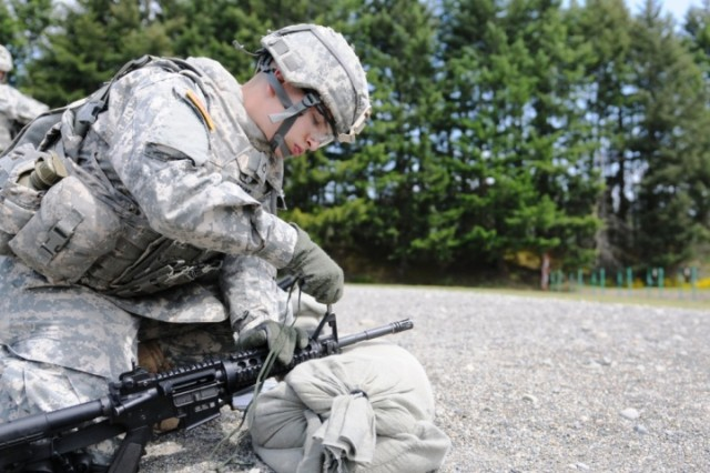 Pfc. David Bradt, a multiple launch rocket system crewmember from Oxford, Conn., adjusts the sights on the M4 he will use during the weapon marksmanship portion of the three-day I Corps Soldier of the Year competition June 7 at Joint Base Lewis-McChord, Wash.
