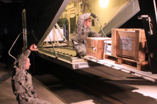 Spc. Charles Brookens, a flight engineer for A Company, 641st Aviation Regiment, and Sgt. Clint Walker, a flight engineer for A Company, 641st, use hand and arm signals to help guide a pallet of cargo onto a C-23 Sherpa during a stop on one of their missions.