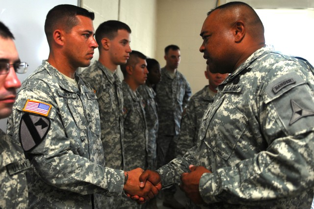 FORT HOOD, Texas - Staff Sgt. Nathan Juroff, a platoon sergeant assigned to the 2nd Battalion, 5th Cavalry Regiment, 1st Brigade Combat Team, 1st Cavalry Division, receives a coin from Command Sgt. Maj. Arthur Coleman, the III Corps Command Sergeant Major