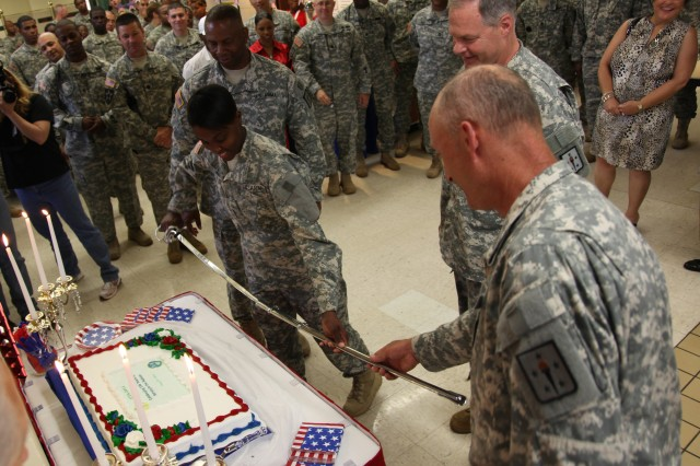 Pfc. Shamari Carmen, the youngest Soldier in the 23rd Quartermaster Brigade, unsheathes the ceremonial sword which will be used to cut the Army Birthday cake in one of the Fort Lee dining facilities June 14. As the crowd looked on, Carmen, along with the Combined Arms Support Command team of Command Sgt. Maj. C.C. Jenkins Jr. (left), Maj. Gen. James L. Hodge (right), and Chief Warrant Officer 5 Michael J. Wichterman (far right), sliced the cake in celebration and honor of the Army's 236 years of preserving peace and freedom.