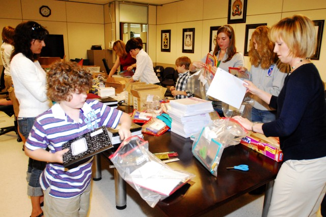 Family Members of Soldiers from 3rd Brigade Combat Team pack school supply kits June 5 in support of Operation Education. The kits will be mailed to Soldiers, who are currently deployed to southern Afghanistan, where they will be handed out to school children.