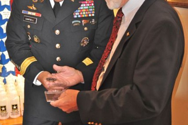 Jim Frazier, Survivor Outreach Services Coordinator, hands Major General John Campbell a coin at the USO of Illinois Navy Pier Center.