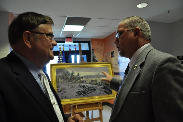 Retired Col. Gary Gresh, right,  speaks to  Kenneth Fidler, with the Adjutant General School, about the newly unveiled Adjutant General regimental print after Friday's Adjutant General Corps Hall of Fame Induction Ceremony. Gresh was among the seven retired officers who were inducted into the Hall of Fame.