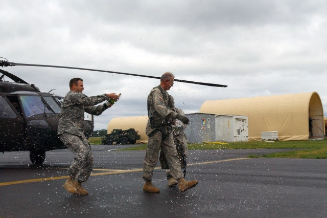LATHAM, NY-- Chief Warrant Officer 5 Steven Derry gets the traditional wetdown with Champagne after completing his final flight on Tuesday, June 14. Derry was the last Vietnam War pilot still flying in the New York Army National Guard.