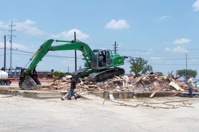 An excavator piles up debris left behind following the demolition of Bldg. 190, at 37th Street and Tank Destroyer Avenue at Fort Hood June 8.