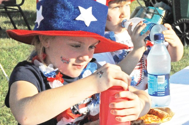 Seantae Foster, daughter of Sgt. 1st Class Chris Foster, attempts to open a water bottle while her brother, Junior, takes a sip of his at last year's Freedom Fest. This year's celebration runs 4-10 p.m. July 2 and will be headlined by Gary Sinise's Lt. Dan Band.