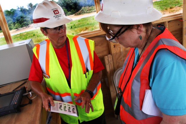 """Park Ranger Ruth """"Pepper"""" Shields (left) from Savannah District's  J. Strom Thurmond Dam and Lake Project, discusses how to assess truck loads of debris with Laura Jo Brunson of FEMA in Rainsville, Ala. While normally a park ranger with Savannah District, Shields volunteered to deploy to Alabama as a quality assurance representative."""
