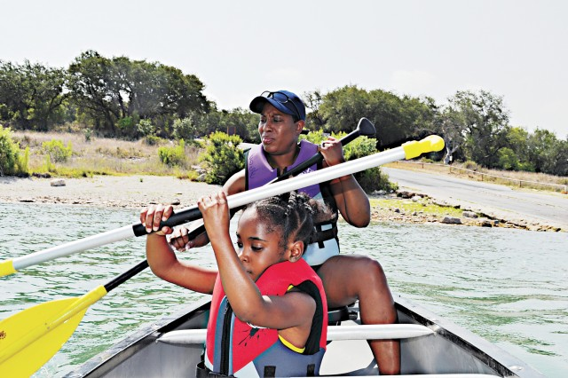 EDGE! Program Director Nita Ford-Hightower teaches 7-year-old Lymaria Sprowl how to paddle a canoe.