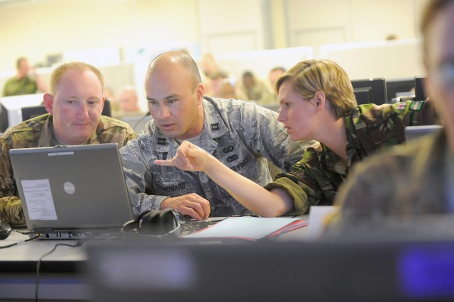 Capt. Nathaniel Chittenden, left, Air Force Capt. Bryan Howard, and British Army Cpl. Lucy Austin, analyze data at the Battle Command Training Center Joint Operation Center during the Unified Endeavor exercise.