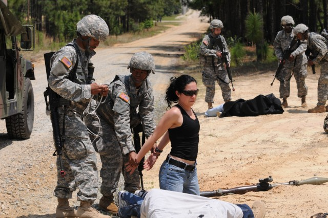 """Members of the 7236th Medical Support Unit apprehend """"enemy combatants,"""" following an ambush of the enemy troops' vehicle during the unit's field training exercise for its noncommissioned officers May 28, at Fort Bragg. The training, which focuses on small-unit tactics, will allow the NCOs to train their subordinates during the unit's annual training later this month."""