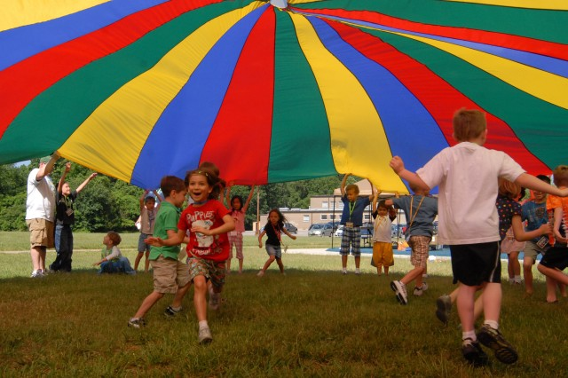 As part of their recreation period on the first day of VBS, children played various games involving a parachute.