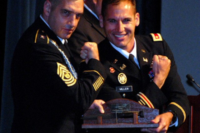 Command and General Staff College Command Sgt. Maj. Philip Johndrow flexes for photographers with Iron Major Award recipient Maj. Scott D. Miller during graduation for the 2011-01 Intermediate Level Education class June 10 in Eisenhower Auditorium, Fort Leavenworth, Kan. Maj. Wilson Low of Singapore also received the Iron Major Award, which recognizes exceptional physical fitness.