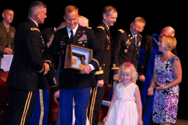 Command and General Staff College Commandant Lt. Gen. Robert Caslen Jr. congratulates top U.S. Intermediate Level Education graduate Maj. Richard Martin, accompanied on stage by his wife Julie Martin and daughters 2-year-old Lydia (shaking CGSC Command Sgt. Maj. Philip Johndrow's hand behind her father) and 6-year-old Lillian, during graduation for ILE class 2011-01 June 10 at the Lewis and Clark Center, Fort Leavenworth, Kan. Martin received the General George C. Marshall Award. Norwegian Capt. Aleksander Jankov received the General Dwight D. Eisenhower Award, presented to the top international graduate.