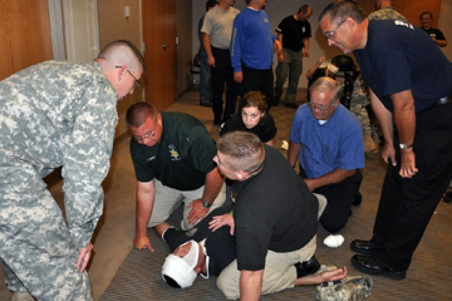 Medical Department Activity Sgt. Jeremy Adkins gives feedback to Cpl. Chris Johnson from the Clay County Sheriff's Office and Jeremiah Fisher from the Riverside, Mo., Police Division during the First Aid - Tactical Combat Care course June 10 at the Platte County Resource Center in Kansas City, Mo. Three MEDDAC Soldiers taught an edited version of the Army's Combat Lifesaver Course to 33 area law enforcement officers and first responders.