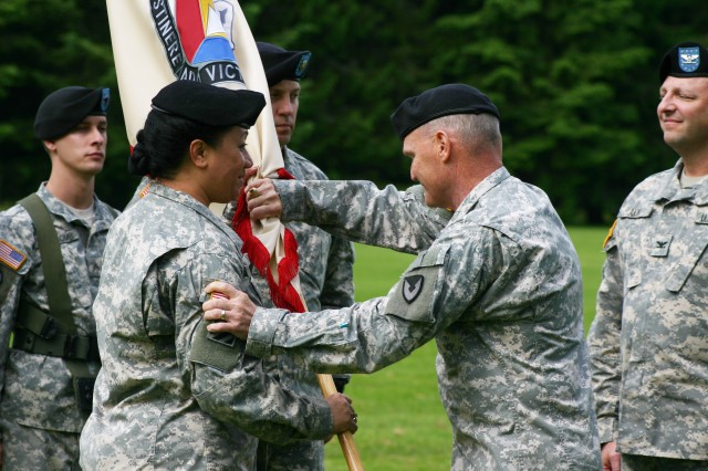Maj. Gen. Yves Fontaine, commanding general of Army Sustainment Command, gestures his congratulations to Col. Leafaina Yahn after he passes the 404th Army Field Support Brigade flag to her during the brigade's change of command ceremony June 15 at Joint Base Lewis-McChord, Wash. Passing the flag to Yahn signifies that she is now commander of the brigade.