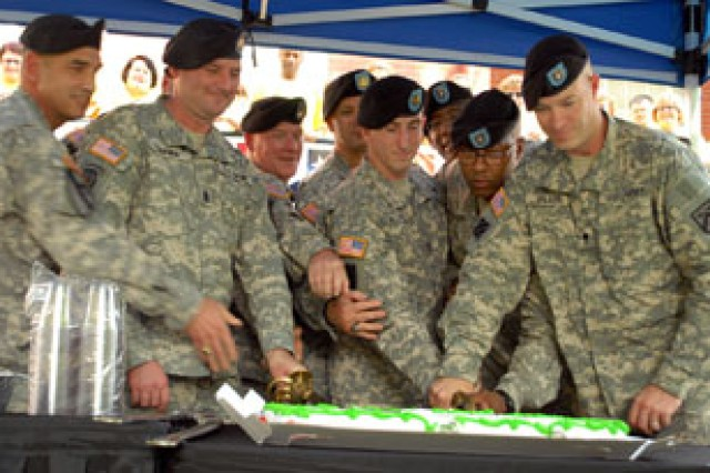 Post sergeants major and Fort Leavenworth's NCO and Soldier of the Year Staff Sgt. Vincent Moore and Spc. James Wilson gather to cut a cake at the ribbon-cutting ceremony signifying the opening of the Resiliency Center June 9 at 600 Thomas Ave. at Fort Leavenworth, Kan.