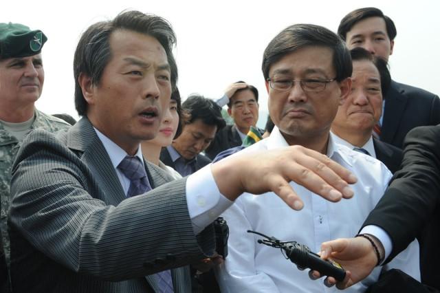 Professor Gon Ok (left) speaks to National Assembly members on Camp Carroll, South Korea, June 9, 2011.