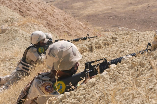 "Soldiers assigned to 1st Battalion, 10th Brigade, 3rd Iraqi Army Division, take cover behind a hill while waiting for ""enemy troops"" during ambush training at Ghuzlani Warrior Training Center, Iraq, June 9, 2011."