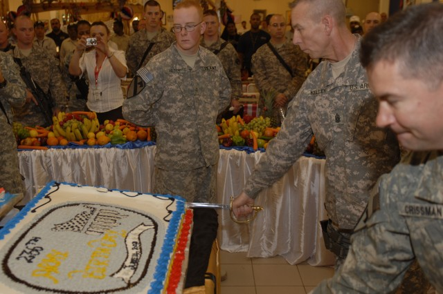 COB ADDER, Iraq - Pfc. Adam Miller from HHT, 3rd AAB, 1st Cav. Div. watches as Col. Douglas C. Crissman, (right) BDE CDR and Command Sgt. Maj. Ronnie R Kelly, (center) slice the Army birthday cake at the Coalition Dinning Facility June 14, 2011.
