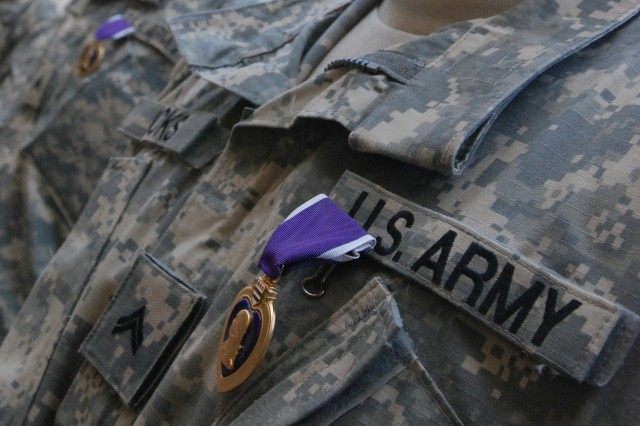 U.S. Army Soldiers from 1st Squadron, 12th Cavalry Regiment, 3rd Brigade Combat Team, 1st Cavalry Division display their newly-presented Purple Hearts at Combat Outpost Bone in Baquba, Iraq, July 13, 2007.