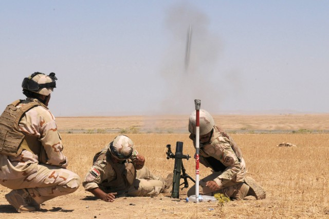Iraqi soldiers assigned to 1st Battalion, 10th Brigade, 3rd Iraqi Army Division, lean away from a mortar tube as a 60mm round blasts into the air during a live-fire exercise at Destiny Range in Ninewa province, Iraq, June 16, 2011.